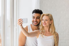 Young Beautiful Couple Stand Window, Taking Selfie Photo On Cell Smart Phone Stock Photos