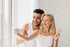 Young Beautiful Couple Stand Window, Taking Selfie Photo On Cell Smart Phone Stock Photo