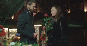 Attractive caucasian couple on a date in a city at night. Young beautiful couple standing on city street at night. Young man choosing flowers for his girlfriend stock video