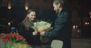 Attractive caucasian couple on a date in a city at night. Young beautiful couple standing on city street at night. Young man choosing flowers for his girlfriend stock footage