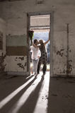 Young beautiful couple standing in doorway with backlighting Royalty Free Stock Photo