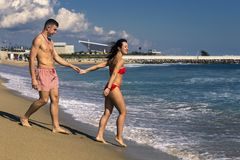 Young and beautiful couple is standing on the sandy beach. stock photos