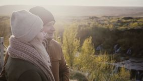 Young beautiful couple standing in sunny valley and talking, enjoying the beautiful view in Iceland. Traveling man and woman exploring the North nature stock video