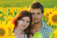 Young beautiful couple in the sunflower field Stock Images