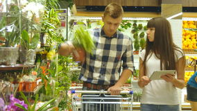 Young beautiful couple with supermarket trolley are choosing indoor plant in the shopping mall. Man is taking and. Viewing houseplants. Woman is using tablet pc stock video footage