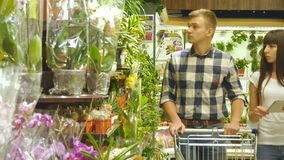 Young beautiful couple with supermarket trolley are walking and choosing indoor plant in the shopping mall. Man is. Taking houseplants. Woman is using tablet pc stock video footage