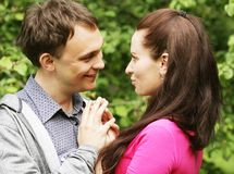 Young beautiful couple in a sweet cheek kiss Royalty Free Stock Image