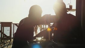 Young beautiful couple takes selfie with smartphone having rest in outdoor beach cafe drinking beer at amazing sunset stock video