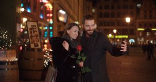 Young beautiful couple taking selfie in a city at night. Young beautiful couple standing on city street at night. Young men and his girlfriend with red rose on Royalty Free Stock Photos