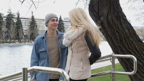 Young beautiful couple talking on a date, standing in a park in a pond. Sexy blonde girl. stock video footage