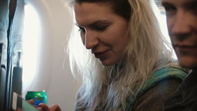 Young beautiful couple traveling by plane. Blonde woman and man sitting near the window and using smartphone. Young beautiful couple traveling by plane. Blonde stock video footage