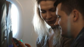 Young beautiful couple traveling by plane together. Happy man and woman using smartphone, planning to see the sights. Male and female exiting about the trip stock video footage