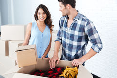 Young beautiful couple unpacking in new flat. Young beautiful happy married couple unpacking in new flat Royalty Free Stock Photo