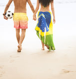 Young beautiful couple walking along beach with brazil flag and football Stock Image