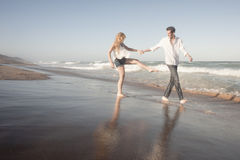 Young beautiful couple walking along beach holding hands Stock Image