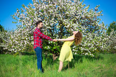Young beautiful couple walking in blooming garden Royalty Free Stock Image