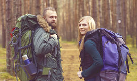 Young beautiful couple walking in forest. Camp, tourism, hiking. Concept Royalty Free Stock Photos