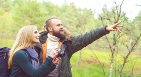 Young beautiful couple walking in forest and taking pictures. Ca Stock Photos