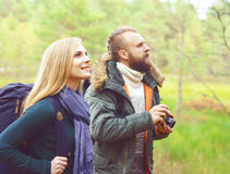 Young beautiful couple walking in forest and taking pictures. Ca Royalty Free Stock Photos