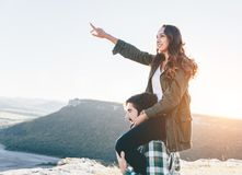 Young beautiful couple walking outside on beautiful sunset. Beautiful woman sittiong on her boyfriend`s shoulders royalty free stock images