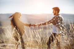Young beautiful couple walking outside on beautiful sunset. Perfect romantic landscape for lovestory. Two hipsters-lovers hugging stock images