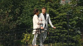 Young beautiful couple walking in the Park and stands on the bridge. Young woman and man walking in city park holding hands stock footage