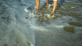 Young beautiful couple walking by the sea. Boy and girl. They are happy. The sun shines brightly. Slow motion. Feet stock footage