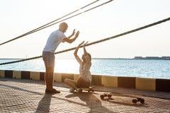 Young beautiful couple walking at seaside, giving highfive, skateboarding. Royalty Free Stock Image
