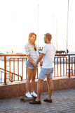 Young beautiful couple walking at seaside, smiling, skateboarding. Stock Photography