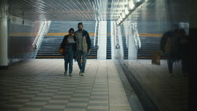 Young beautiful couple walking through the underground passage and looking on the map. Tourists in new city. stock video