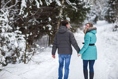 Young beautiful couple walking in winter forest Royalty Free Stock Image