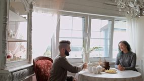 Young beautiful couple in warm sweaters in a country house are sitting at the white table against the background of the. Window. The family drinks tea from stock footage