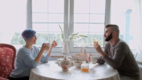 Young beautiful couple in warm sweaters in a country house are sitting at the white table against the background of the. Window. The family drinks tea from stock video