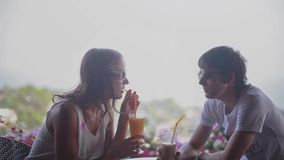 Young beautiful couple wearing sunglasses with smartphone talking and drinking cocktails sitting in an outdoor cafe. Young beautiful couple with smartphone stock footage
