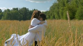 Young beautiful couple in white clothes hugging in on a wheat field stock footage
