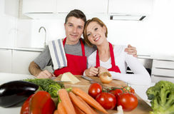 Young beautiful couple working at home kitchen preparing vegetable salad together smiling happy Stock Photo