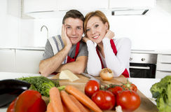 Young beautiful couple working at home kitchen preparing vegetable salad together smiling happy. Young beautiful American couple working at home kitchen in red royalty free stock photography