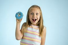 Young beautiful happy and excited blond girl 8 or 9 years old holding donut desert on her hand looking spastic and cheerful in sug. Young beautiful crazy happy royalty free stock photo