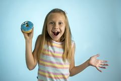 Young beautiful happy and excited blond girl 8 or 9 years old holding donut desert on her hand looking spastic and cheerful in sug. Young beautiful crazy happy royalty free stock photos