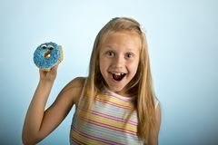Young beautiful happy and excited blond girl 8 or 9 years old holding donut desert on her hand looking spastic and cheerful in sug. Young beautiful crazy happy stock image