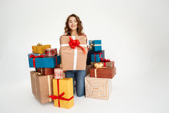 Young beautiful curly girl among gift boxes over white background Royalty Free Stock Photography