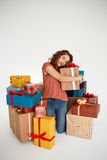 Young beautiful curly girl among gift boxes over white background Royalty Free Stock Image