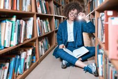 Young beautiful curly girl in glasses and blue suit sitting with books in the library. stock photography