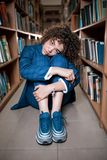 Young beautiful curly girl in glasses and blue suit sitting with books in the library. stock photos