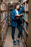 Young beautiful curly girl in glasses and a blue suit is standing in the library royalty free stock photos