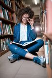 Young beautiful curly girl in glasses and blue suit sitting with books in the library. royalty free stock image