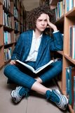 Young beautiful curly girl in glasses and blue suit sitting with books in the library. stock images
