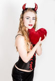 Young and beautiful curly girl with red horns looks like pretty Devil, holding a heart pillow Royalty Free Stock Photography