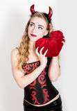Young and beautiful curly girl with red horns looks like pretty Devil, holding a heart pillow Stock Photos