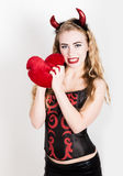 Young and beautiful curly girl with red horns looks like pretty Devil, holding a heart pillow Stock Photography